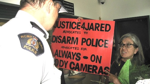 RCMP officer looms over female protester