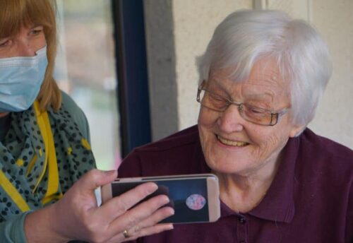A young woman,, wearing a mask, showing an older woman something on a cell phone