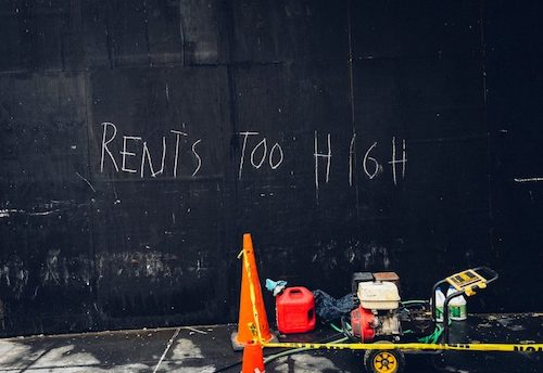 Black wall with the words 'Rents too high' written on it